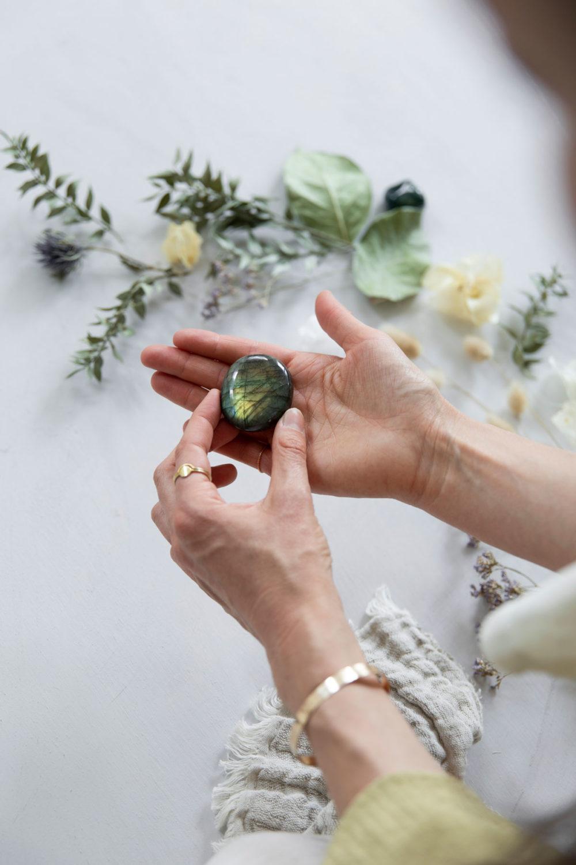 CREATE YOUR MAGIC – Dein Labradorit Edelstein crystal. Mood, Hände, goldene Ringe und Armreif, Decke, Trockenblumen, Blätter, Distel, Moosachat Stein, NAIONA.