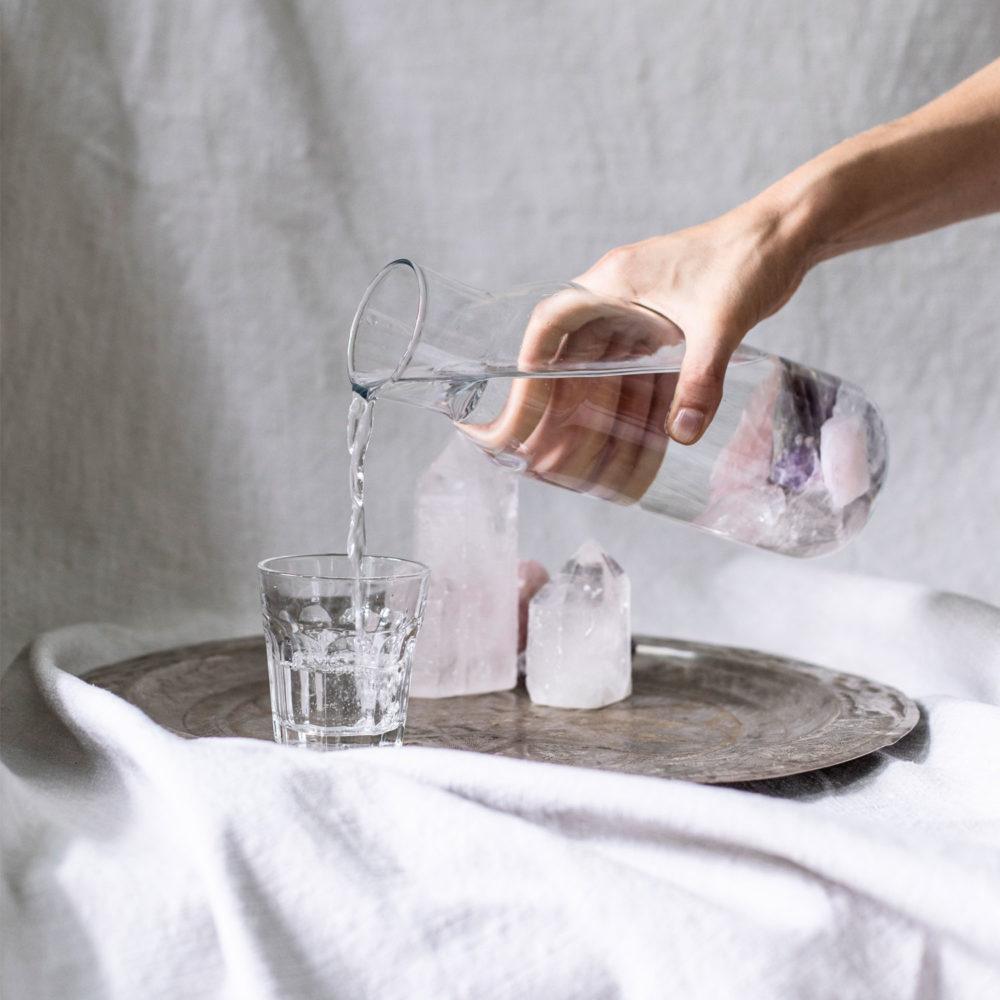 Wassersteine – BE WATER, MY FRIEND mit Bergkristall, Rosenquarz und Amethyst Steinen. Wasser, Reinigen, Karaffe, Hand, Tablett, Tuch, Glas, Bergkristallspitze, NAIONA.