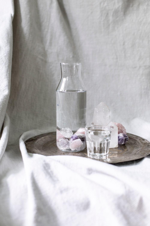 Wassersteine – BE WATER, MY FRIEND mit Bergkristall, Rosenquarz und Amethyst Steinen. Wasser, Reinigen, Edelsteine, Karaffe, Tablett, Tuch, Glas, Bergkristallspitze, NAIONA.