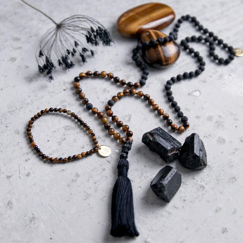 STRONG DECISION Mala und Armband aus Lava und Tigerauge Steinen mit schwarzem Turmalin, schwarzer Quaste und goldenem NAIONA Plättchen und Turmalin und Tigerauge Steinen und Trockenblumen.