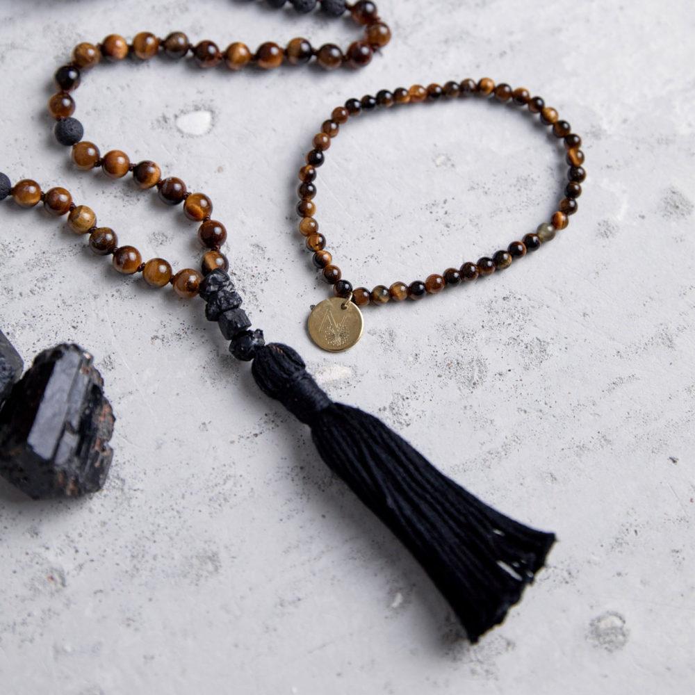 STRONG DECISION Mala und Armband aus Lava und Tigerauge Steinen mit schwarzem Turmalin, schwarzer Quaste und goldenem NAIONA Plättchen und Turmalin Steinen.