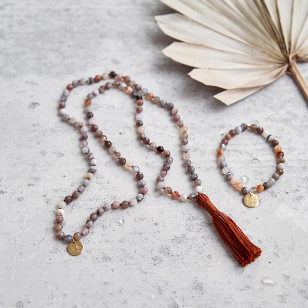 BALANCE Mala aus Achat Steinen mit Quaste und goldenem Plättchen und Armband aus Achat Steinen mit goldenem NAIONA Plättchen und Trockenblume.