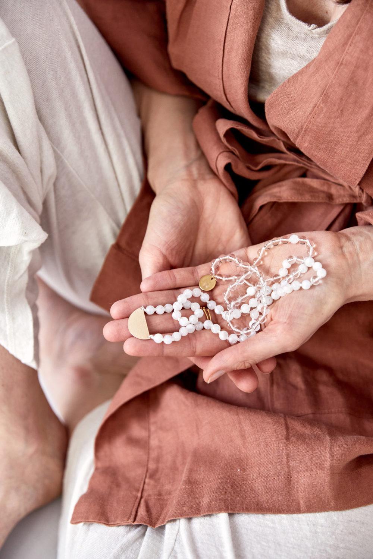 CLEAR SEEING Mala aus weißen Mondsteinen und Bergkristall Steinen mit goldenem Halbmond und NAIONA Plättchen. Mood, Pose, Ausschnitt, Kleid, Hände, Ringe, Hemd, Kimono.