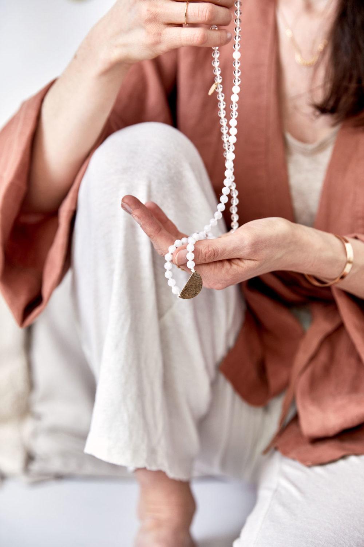 CLEAR SEEING Mala aus weißen Mondsteinen und Bergkristall Steinen mit goldenem Halbmond und NAIONA Plättchen. Mood, Pose, Ausschnitt, Kleid, Hände, Ringe, Hemd, Kimono goldener MOONCHILD Armreif und Kette mit Mondphasen.