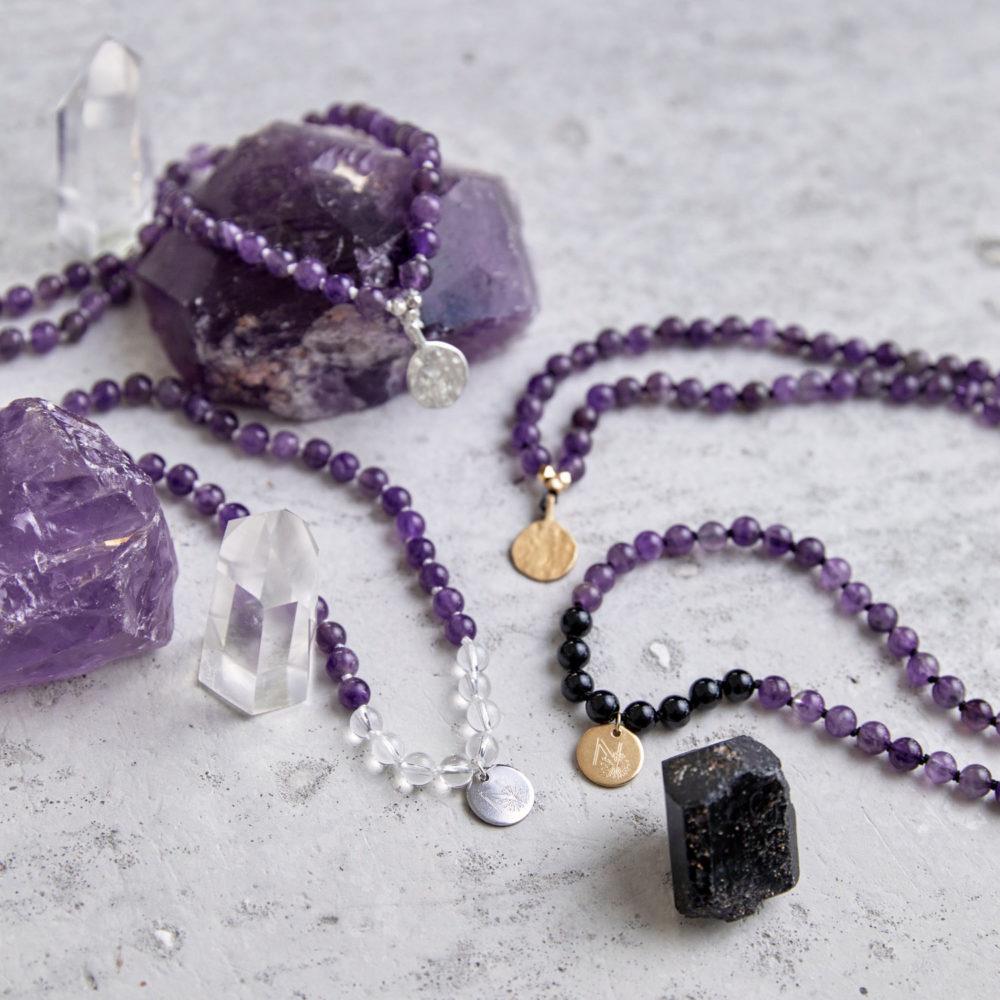 PEACE OF MIND Mala aus Amethyst und Bergkristall Steinen mit silbernen NAIONA Plättchen und Perlen und Mala aus Amethyst und Turmalin Steinen mit goldenen Plättchen und Perlen und Amethyst und Turmalin Steine und Bergkristallspitzen.
