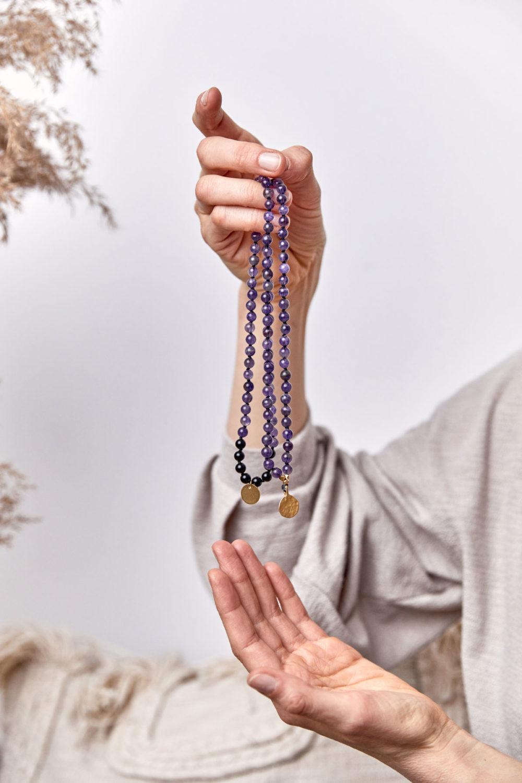 PEACE OF MIND Mala aus Amethyst und schwarzen Turmalin Steinen mit goldenen NAIONA Plättchen und Perlen. Mood, Pose, Hemd, Hände, Decken, Kissen, Trockenblumen.