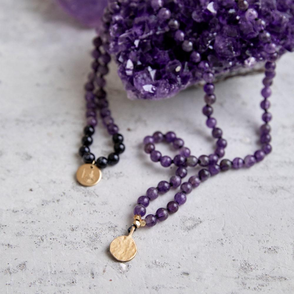 PEACE OF MIND Mala aus Amethyst und schwarzen Turmalin Steinen mit goldenen NAIONA Plättchen und Perlen und Amethyst Stufe.