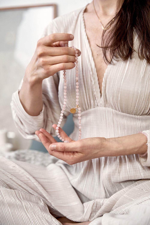 TRUE LOVE Mala aus Rosenquarz Steinen mit goldenen NAIONA Plättchen und Perlen und MOONCHILD Kette. Mood, Pose, Ausschnitt, Hände, Kleid.