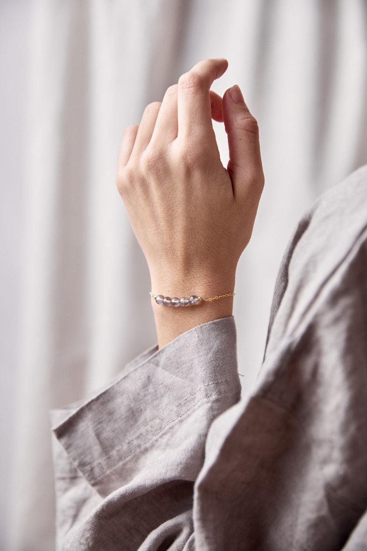 CREATE YOUR MAGIC Armband gold mit Labradorit Steine und goldenem Plättchen. Pose, Arm, Handgelenk, Bluse, NAIONA.