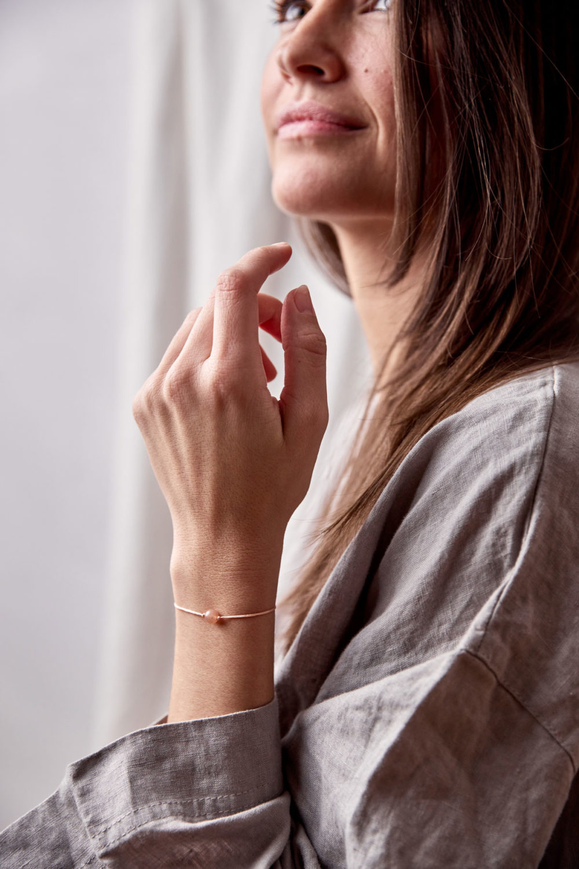 FEMININE AWAKENING Armband verstellbares Schiebearmband mit Mondstein rosé und rosa Band. NAIONA, Pose, Handgelenk, Bluse.
