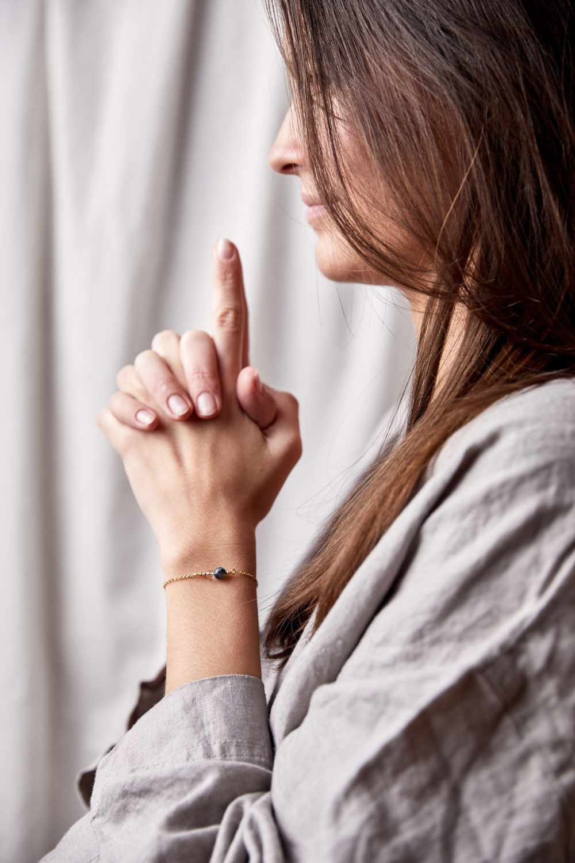 FREE YOURSELF Armband gold fein mit Bergkristall und Moosachat und goldenem NAIONA Plättchen. Pose, Hände, Handgelenk.