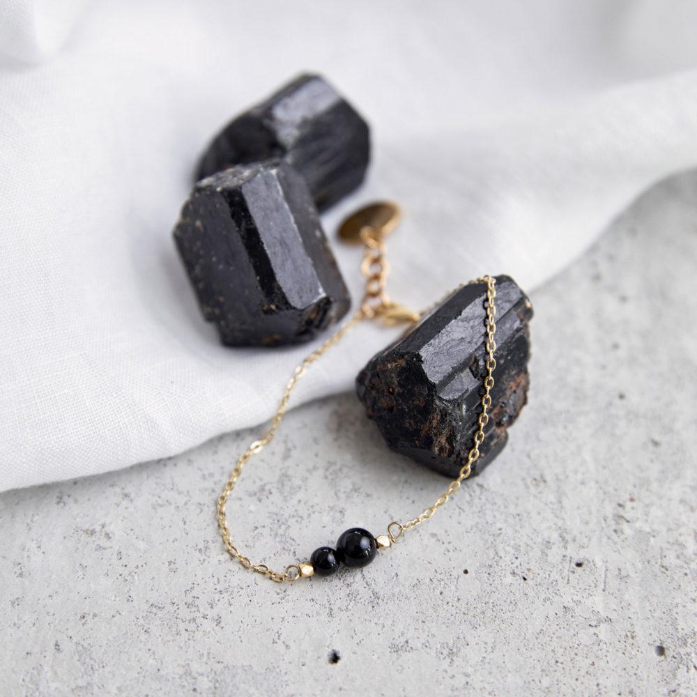 INNER PEACE KEEPER Armband gold fein mit schwarzen Turmalin Steinen und goldenem NAIONA Plättchen. Tuch, Turmalin Steinen.