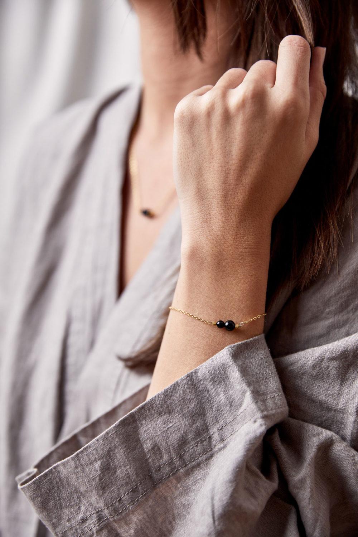 INNER PEACE KEEPER Armband gold fein und Kette mit schwarzen Turmalin Steinen und goldenem NAIONA Plättchen. Hand, Handgelenk, Pose, Bluse.