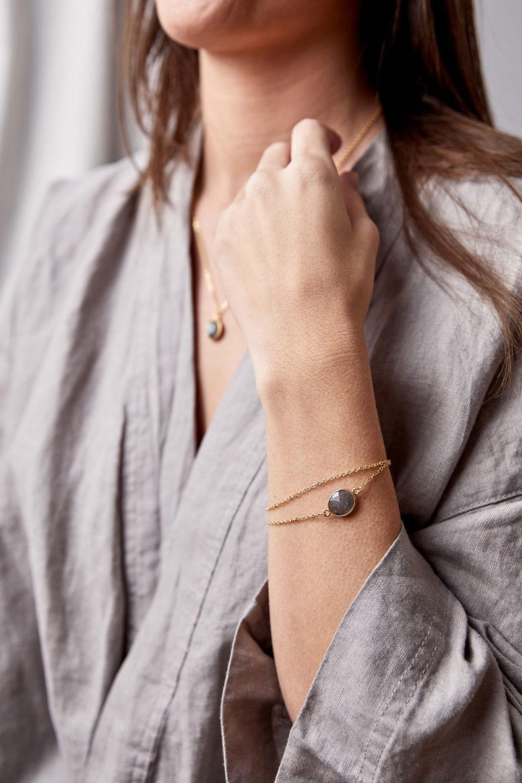 KAUPO Armband gold mit Labradorit grau und goldenem NAIONA Plättchen und KAUPO Kette gold. Pose, Frau, Hand, Handgelenk, Bluse.