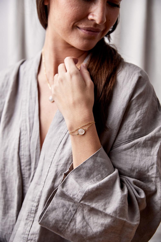 KAUPO Armband gold mit Mondstein weiß und goldenem NAIONA Plättchen und KAUPO Kette gold. Pose, Frau, Hand, Handgelenk, Bluse.
