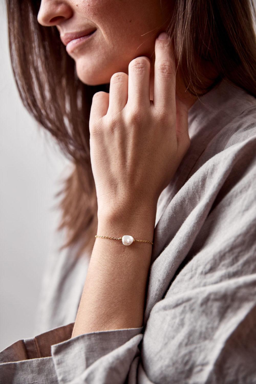 MALIA Armband gold mit Süßwasserperle, goldenem NAIONA Plättchen und Perlen. Pose, Hand, Handgelenk.