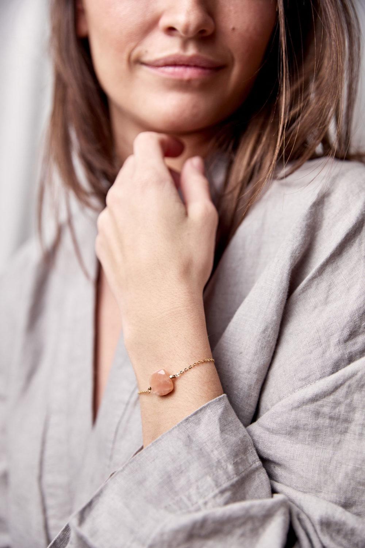 PAUKAA Armband gold mit Mondstein rosé und goldenem NAIONA Plättchen. Pose, Arm, Handgelenk, Bluse.