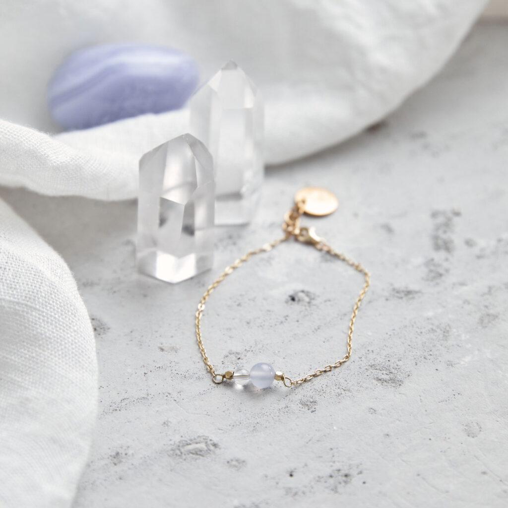 SPEAK UP Armband fein gold mit blauem Chalcedon und Bergkristall Stein und goldenem NAIONA Plättchen. Bergkristallspitze, Chalcedon, Tuch.