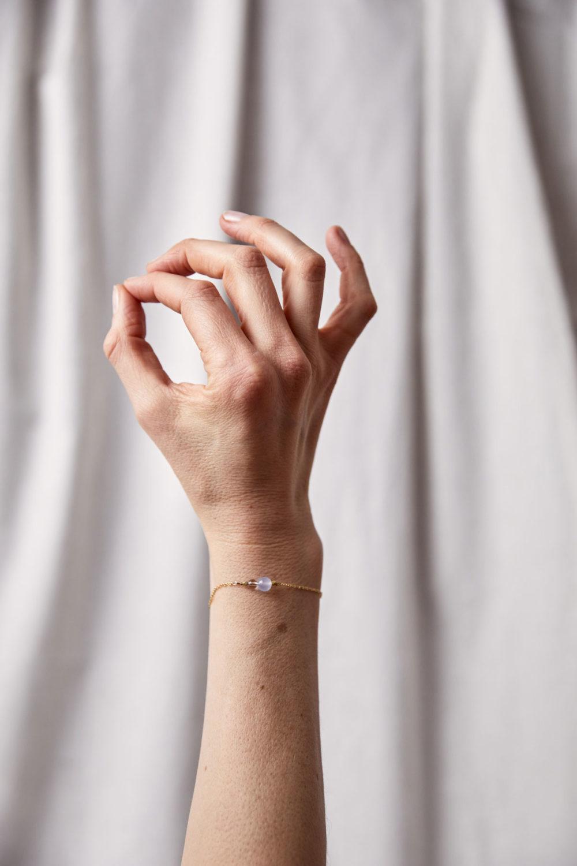 SPEAK UP Armband fein gold mit blauem Chalcedon und Bergkristall Stein und goldenem NAIONA Plättchen. Pose, Hand, Ohm.