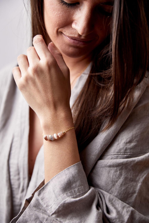 YIN GUIDANCE Armband gold mit Mondstein Splittern und goldenem NAIONA Plättchen. Pose, Frau, Handgelenk, Bluse.