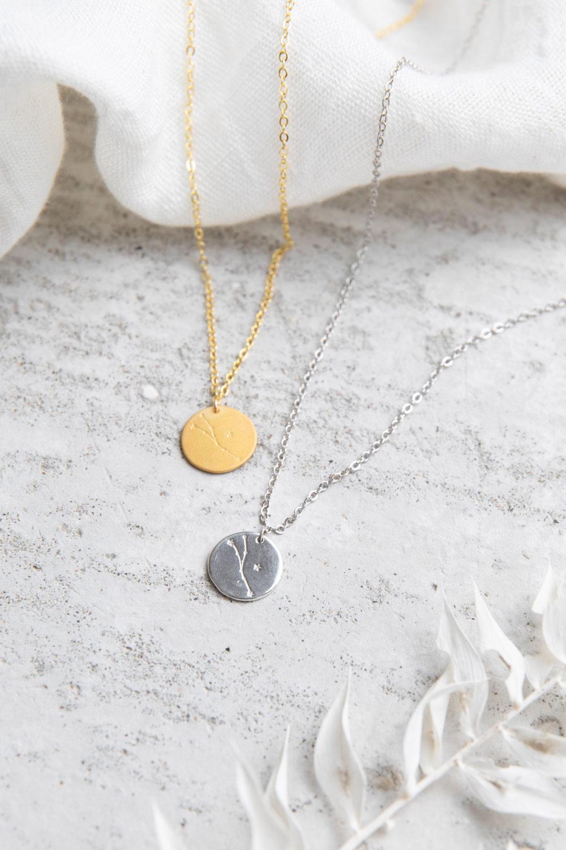 COSMIC COLLECTION STIER Kette gold und mit goldenem oder silbernem Plättchen mit graviertem Stier-Sternzeichen und NAIONA Plättchen. Tuch, Trockenblumen.