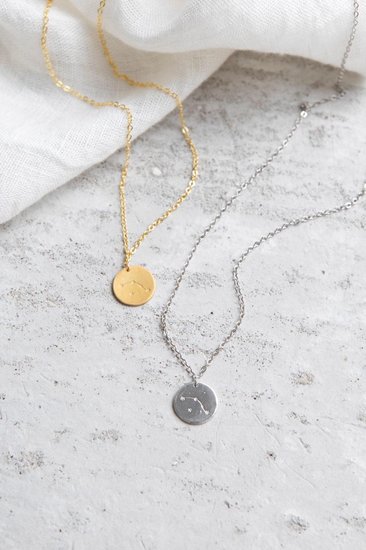COSMIC COLLECTION WIDDER Kette gold und mit goldenem oder silbernem Plättchen mit graviertem Widder-Sternzeichen und NAIONA Plättchen. Tuch.
