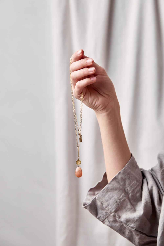AWALUA Kette gold mit Mondstein rosé und goldenem gehämmerten Plättchen und NAIONA Plättchen. Arm, Hand, Hemd.