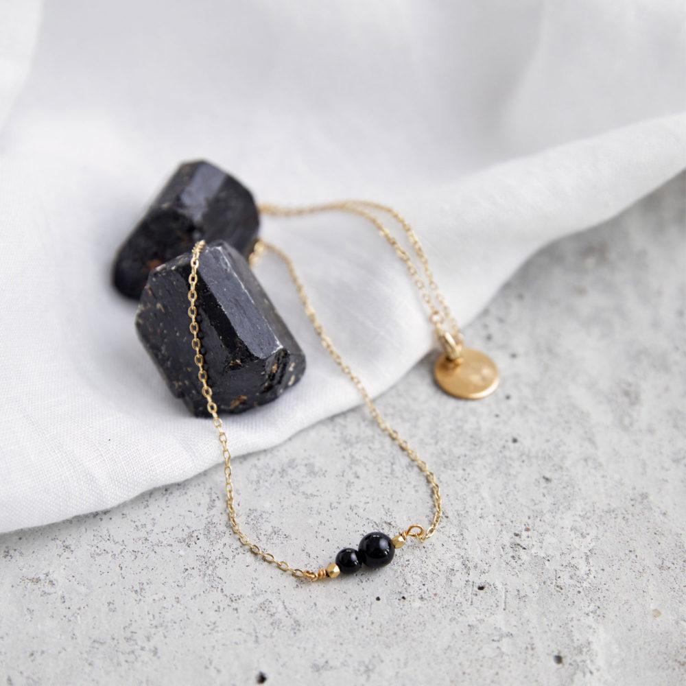 INNER PEACE KEEPER Kette gold fein mit schwarzen Turmalin Steinen und goldenem NAIONA Plättchen und Perlen. Tuch, Turmalin Steine schwarz.