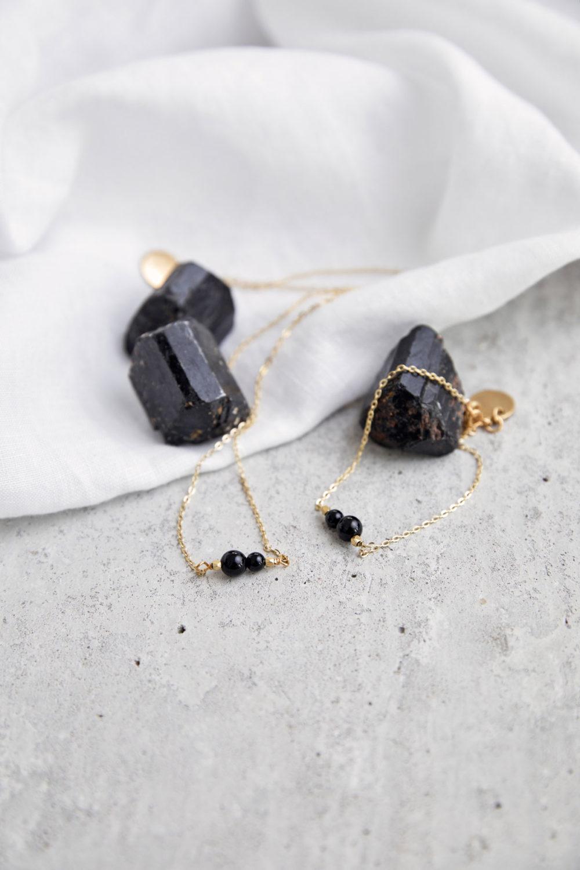 INNER PEACE KEEPER Kette gold fein und Armband mit schwarzen Turmalin Steinen und goldenem NAIONA Plättchen und Perlen. Tuch, Turmalin Steine schwarz.
