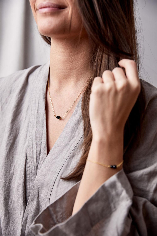 INNER PEACE KEEPER Kette gold fein und Armband mit schwarzen Turmalin Steinen und goldenem NAIONA Plättchen und Perlen. Hand, Handgelenk, Pose, Ausschnitt, Bluse.