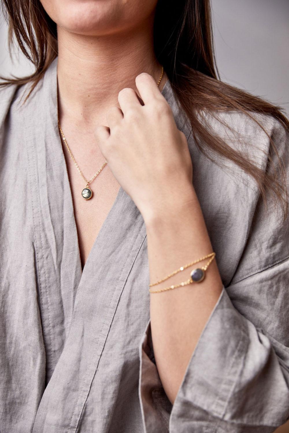 KAUPO Kette gold klein mit Labradorit Stein grau und goldenem NAIONA Plättchen und KAUPO Armband gold. Pose, Frau, Hand, Handgelenk, Hemd.