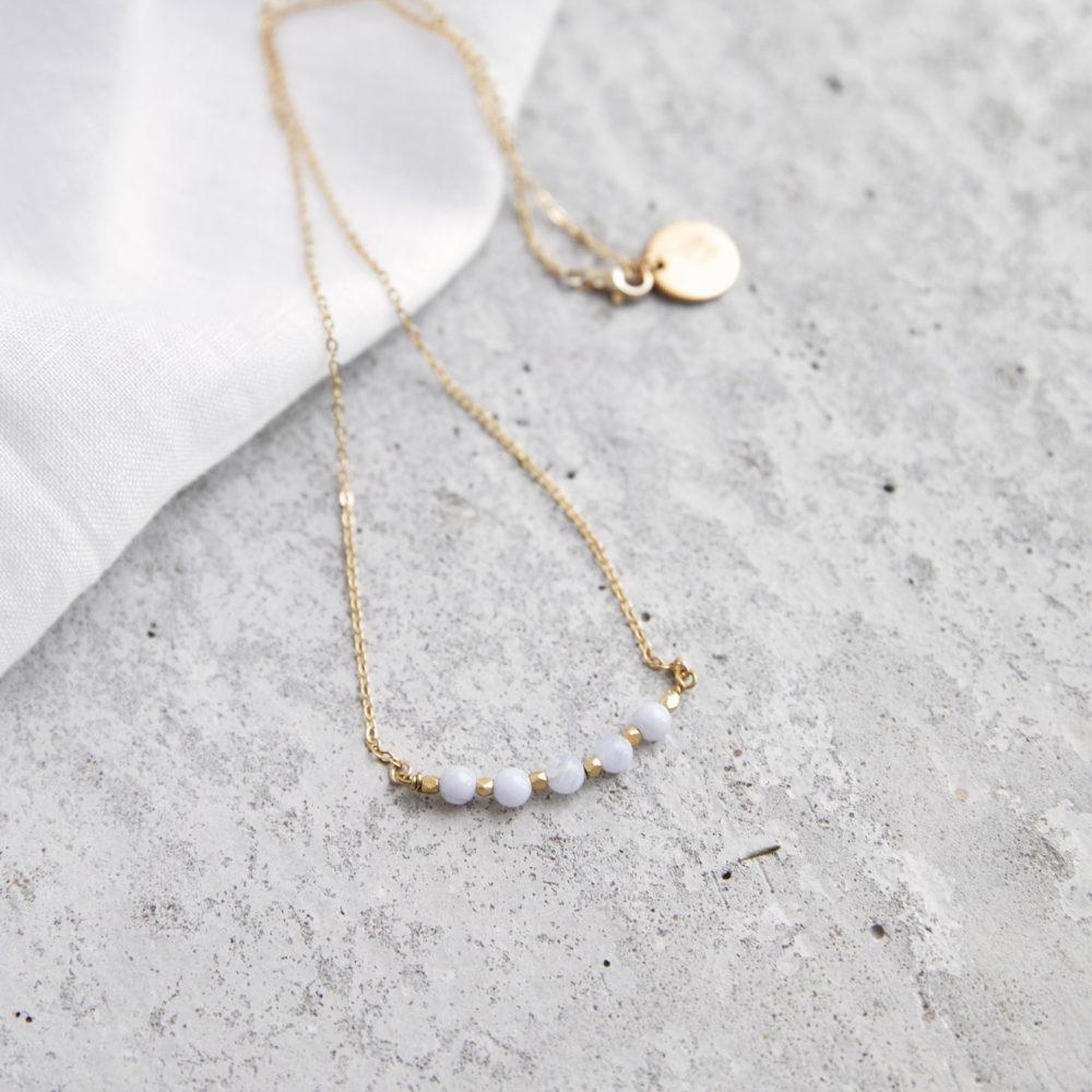 KUALA Kette gold mit kleinen Chalcedon Steinen und goldenen Perlen und NAIONA Plättchen. Tuch.