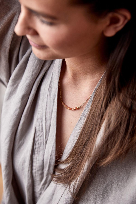 KUALA Kette gold mit kleinen Mondstein rosé Steinen und goldenen Perlen und NAIONA Plättchen. Frau, Ausschnitt, Hemd.