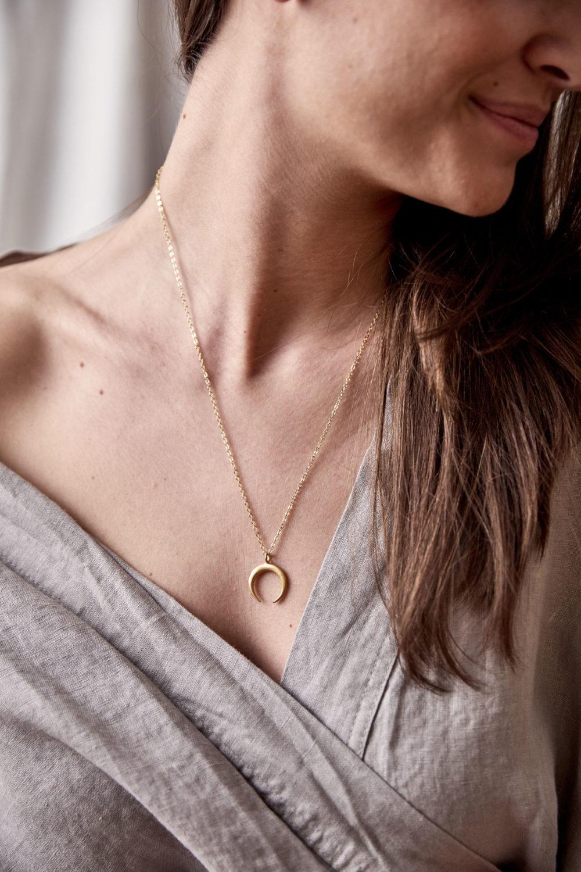 LUA Kette gold mit goldenem Mond und NAIONA Plättchen. Frau, Ausschnitt, Hemd.