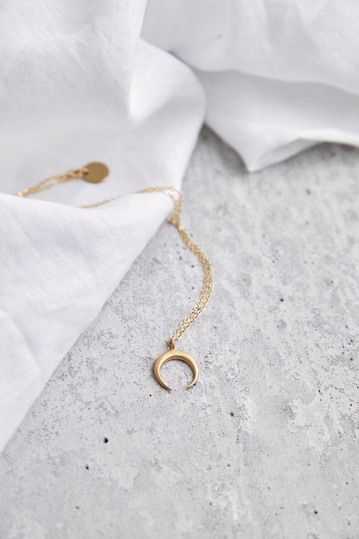 LUA Kette gold mit goldenem Mond und NAIONA Plättchen. Tuch.