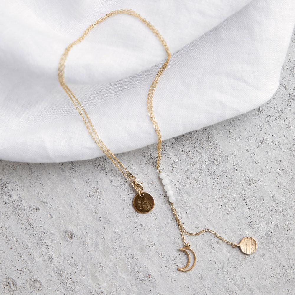 MAHINA HOU Kette gold mit goldenem Plättchen, Mond NAIONA Plättchen und kleinen Mondstein Steinen weiß. Tuch.