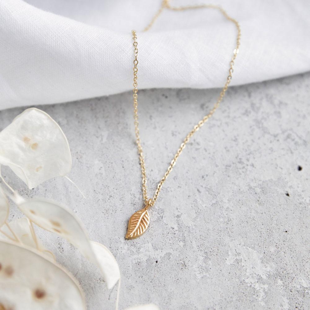 MANOA Kette gold mit goldenem Blatt und NAIONA Plättchen. Tuch, Trockenblumen.