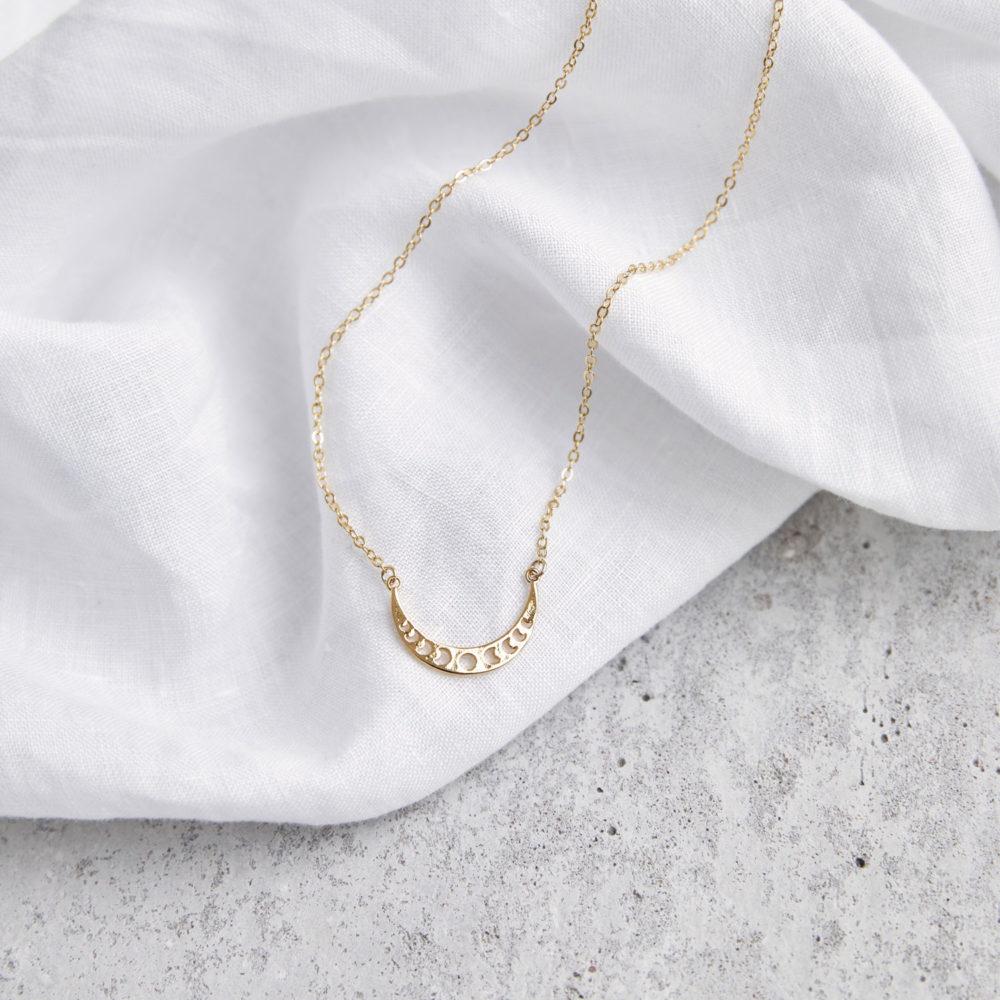 MOONCHILD Kette gold mit goldenen Mondphasen und NAIONA Plättchen. Tuch.