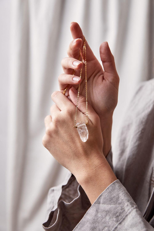 NELIO Kette gold mit Bergkristallspitze, goldenen Perlen und NAIONA Plättchen. Hände, Hemd, Haltung.
