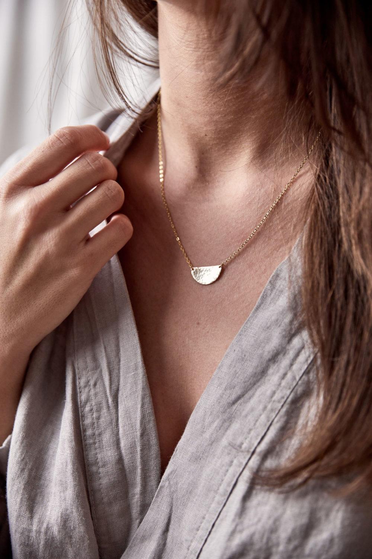 SIMPLICITY Kette gold mit goldenem Halbmond Plättchen und NAIONA Plättchen. Frau, Ausschnitt, Hemd.