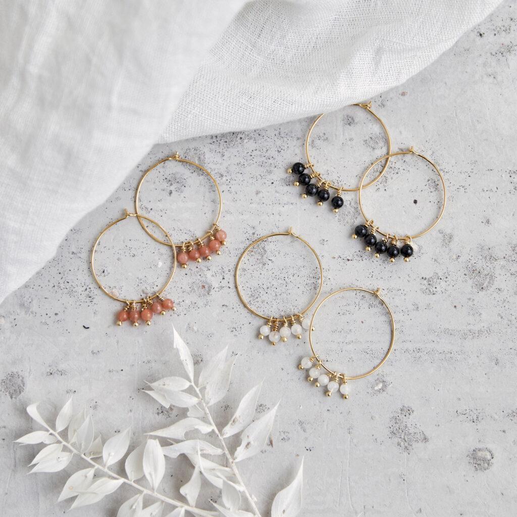 ALUNA Ohrringe gold mit Mondstein weiß und rosé und Turmalin Steinen. NAIONA, Kreolen, Tuch, Trockenblumen.
