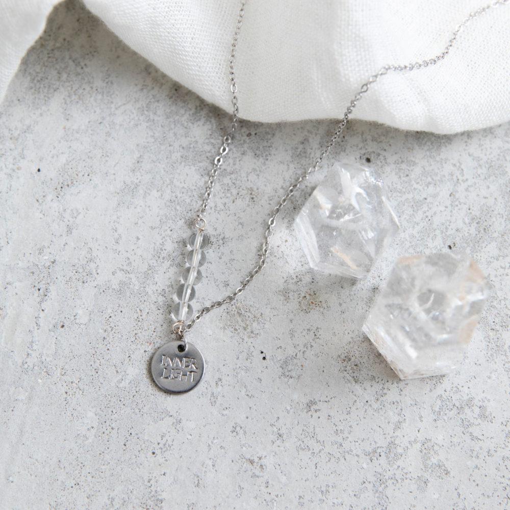 STATEMENT COLLECTION INNER LIGHT Kette silber mit silbernem geprägten Plättchen und NAIONA Plättchen und Bergkristall Steinen Perlen. Tuch, Bergkristallspitzen.