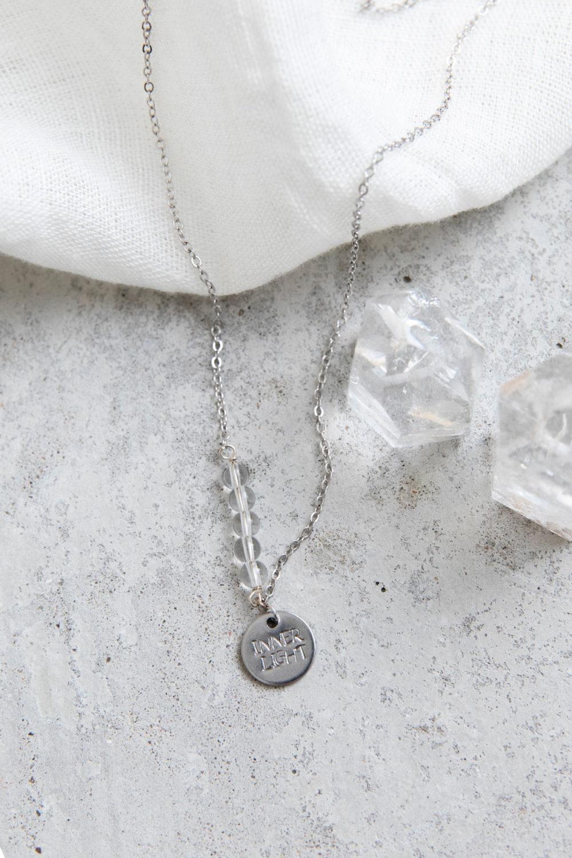STATEMENT COLLECTION INNER LIGHT Kette silber mit silbernem geprägten Plättchen und NAIONA Plättchen und Bergkristall Steinen Perlen. Tuch.