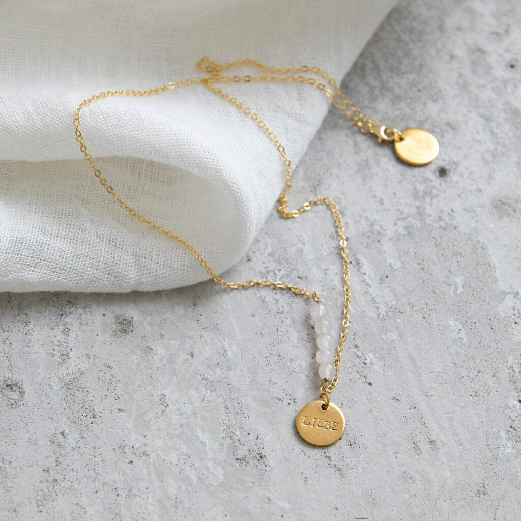 STATEMENT COLLECTION LIEBE Kette gold mit goldenem geprägten Plättchen und NAIONA Plättchen und Mondstein weiß Steinen. Tuch.
