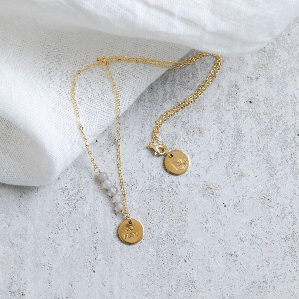 STATEMENT COLLECTION SO HAM Kette gold mit goldenem geprägten Plättchen und NAIONA Plättchen und Achat Steinen. Tuch.